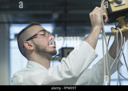Young male scientist working in a pharmacy laboratory, Freiburg Im Breisgau, Baden-Württemberg, Germany - Stock Photo