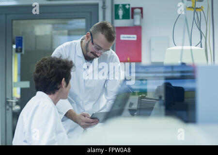 Two scientist working on digital tablet in a pharmacy laboratory, Freiburg Im Breisgau, Baden-Württemberg, Germany - Stock Photo