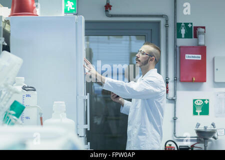 Young male scientist reading notes in a pharmacy laboratory, Freiburg Im Breisgau, Baden-Württemberg, Germany - Stock Photo