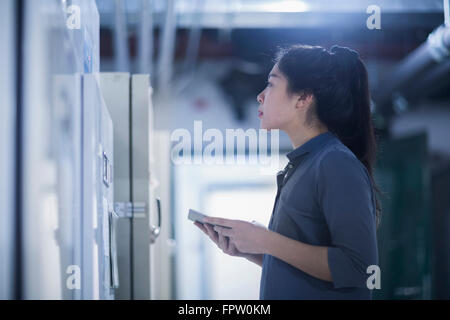 Young female engineer updating control panel by digital tablet in an industry, Freiburg Im Breisgau, Baden-Württemberg, - Stock Photo