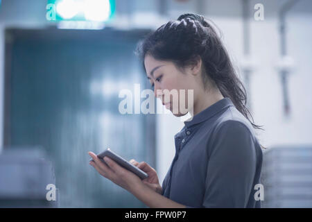 Young female engineer using digital tablet in an industrial plant, Freiburg Im Breisgau, Baden-Württemberg, Germany - Stock Photo