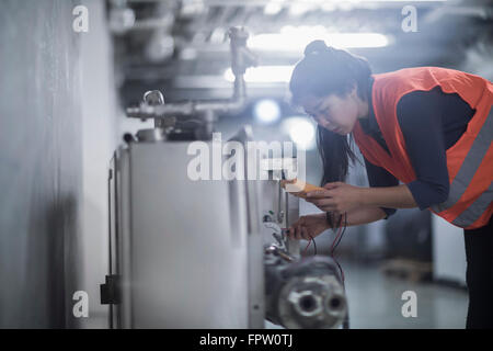 Young female engineer examining machine with multimeter in an industrial plant, Freiburg Im Breisgau, Baden-Württemberg, - Stock Photo