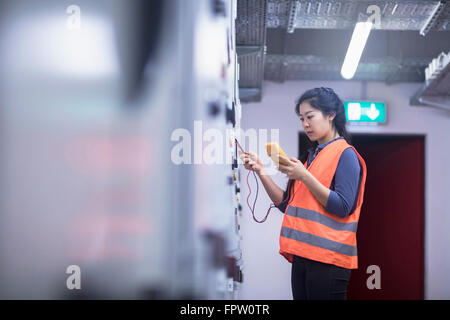 Young female engineer examining control panel with multimeter in an industrial plant, Baden-Württemberg, Germany - Stock Photo