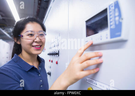 Young female engineer working at control panel in an industrial plant, Freiburg Im Breisgau, Baden-Württemberg, - Stock Photo