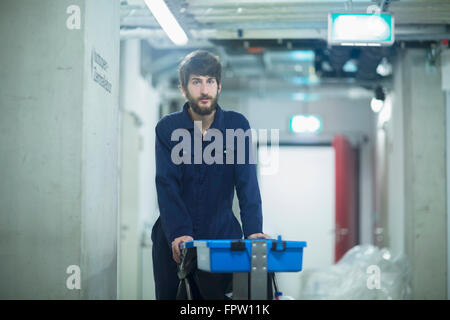 Young male cleaning staff standing with trash can in an industrial plant, Freiburg Im Breisgau, Baden-Württemberg, - Stock Photo