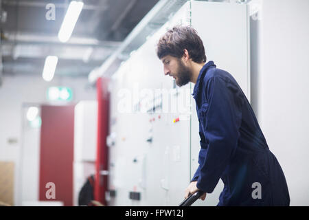 Young male engineer pushing cart in an industrial plant, Freiburg Im Breisgau, Baden-Württemberg, Germany - Stock Photo