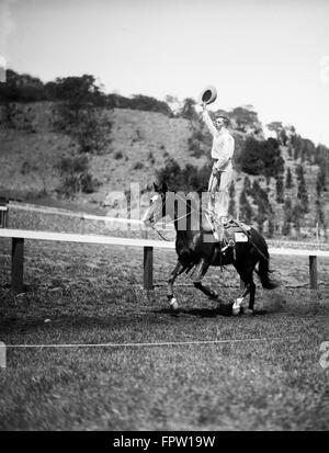 1930s JIM ROGERS SON OF ACTOR WILL ROGERS PERFORMING STUNT TRICK STANDING ON GALLOPING HORSE BACK WAVING COWBOY - Stock Photo