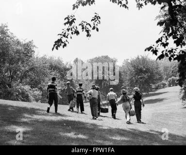 1950s GROUP OF EIGHT TEENAGE KIDS BOYS GIRLS WALKING IN SUMMER SUNLIT FIELD CARRYING PICNIC BASKETS - Stock Photo