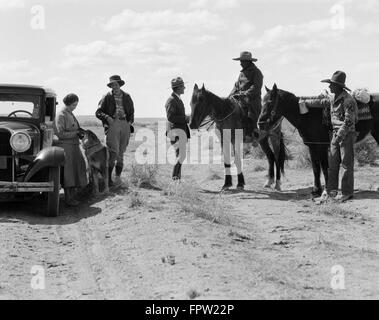 1930s TWO NATIVE AMERICAN NAVAJO INDIAN MEN WITH PONIES STOP TO SPEAK TO PARK RANGER WITH TWO WOMEN TOURISTS - Stock Photo