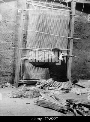 1930s NATIVE AMERICAN NAVAJO WOMAN SEATED AT LOOM WEAVING A RUG - Stock Photo