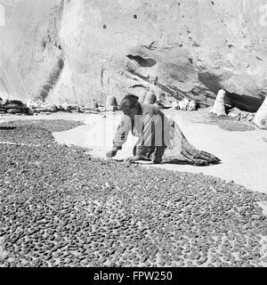 1930s KNEELING NATIVE AMERICAN INDIAN NAVAJO WOMAN DRYING PEACHES CANYON DEL MUERTO ARIZONA USA - Stock Photo