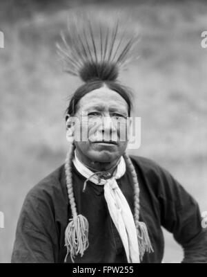 1920s PORTRAIT HANDSOME NATIVE AMERICAN INDIAN MAN OF KOOTENAY TRIBE WEARING FEATHERS AND BRAIDS LOOKING AT CAMERA - Stock Photo