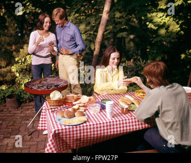1970S TWO COUPLES HAVING BACKYARD PICNIC - Stock Photo