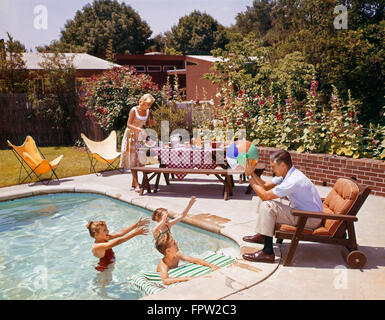 1950s 1960s MAN FATHER TOSSING BALL TO THREE CHILDREN IN SWIMMING POOL MOTHER FIXING PICNIC LUNCH SUBURBAN BACKYARD - Stock Photo