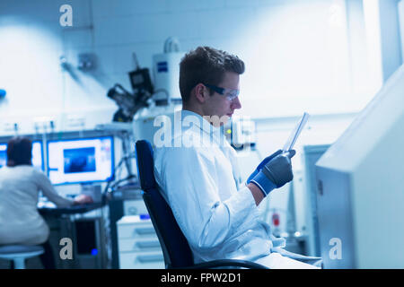 Young male scientist looking at report in an optical laboratory, Freiburg Im Breisgau, Baden-Württemberg, Germany - Stock Photo