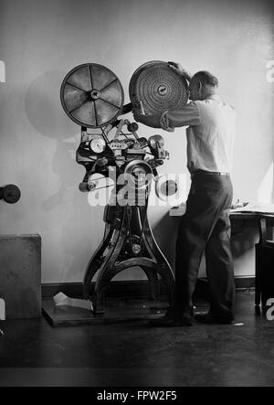 1930s MAN RUNNING LARGE SPECIALTY ADDRESS LABEL PRINTING MACHINE WHICH CAN PRINT 125 000 SUBSCRIBER NAME LABELS - Stock Photo