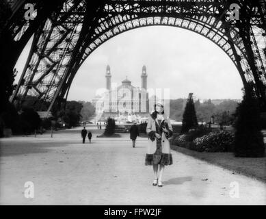 1920s WOMAN WALKING UNDER THE EIFFEL TOWER WITH THE TROCADERO IN BACKGROUND PARIS FRANCE - Stock Photo