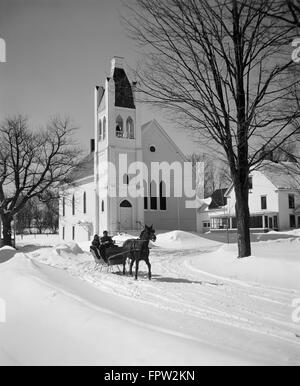 1960s COUPLE DRIVING ONE-HORSE SLEIGH IN FRONT OF COUNTRY CHURCH - Stock Photo