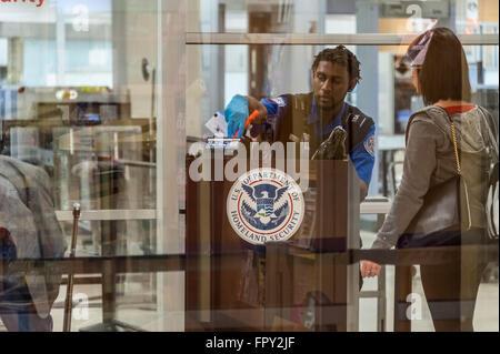 TSA agent verifies passenger credentials at Hartsfield-Jackson Atlanta International Airport. - Stock Photo