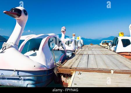 Swan pedal boats berthed to a pier on Lake Tazawa in Akita, Japan - Stock Photo