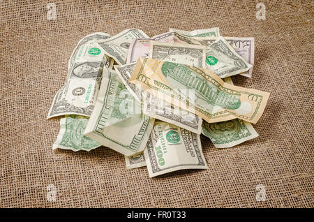 Pile of US dollar banknotes crumpled on rustic jute background - Stock Photo