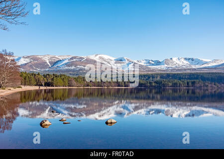 Loch Morlich in the Cairngorms region of Scotland on a calm and sunny spring day with part snow covered Cairn Gorm - Stock Photo