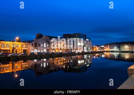 The illuminated buildings of Union Quay, Cork city, Ireland a blue sky reflected in the dark blue waters of the - Stock Photo