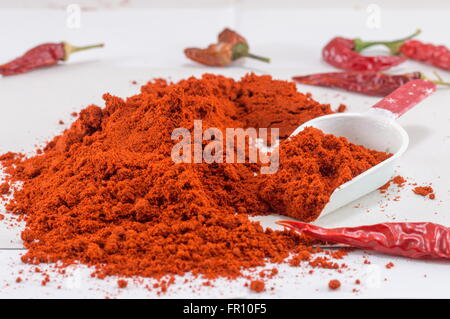 Pile of grounded red pepper and fresh peppers - Stock Photo