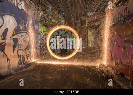 Silhouette of man spinning illuminated wire wool at night inside graffitti tunnael Waterloo in London, UK - Stock Photo
