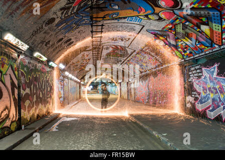 Silhouette of man spinning illuminated wire wool at night inside graffiti tunnel Waterloo in London, UK - Stock Photo