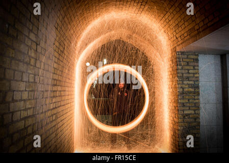 Silhouette of man spinning illuminated wire wool at night at tunnel under Westminster Bridge near Big Ben Houses - Stock Photo