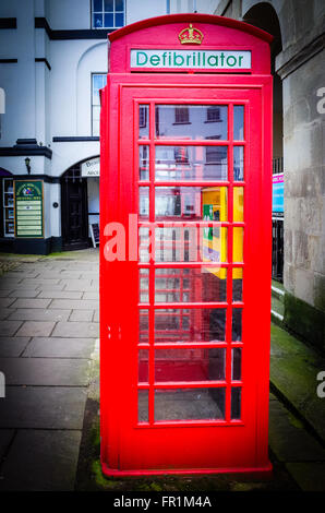 Defibrillator. Old red British phone box converted to accommodate a community defibrillator. - Stock Photo