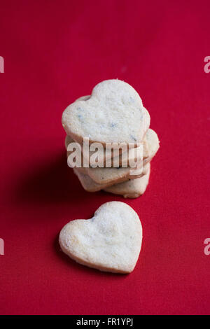 Heart shaped biscuits on a red background. - Stock Photo