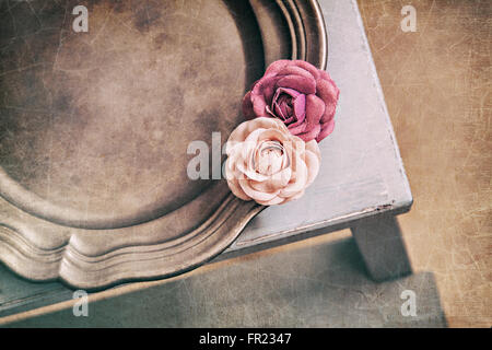 Image of vintage styled flat lay still life with fabric roses on tin platter. - Stock Photo