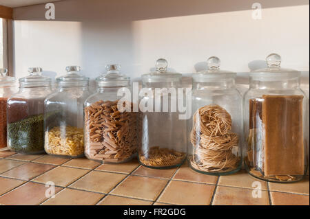 row of large glass kitchen jars in a row with red green lentils and pasta shells tagatelli - Stock Photo