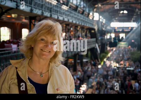 Woman having fun in the hall of the Sunday fish market (Fischmarkt), St Pauli, Hamburg, Germany - Stock Photo