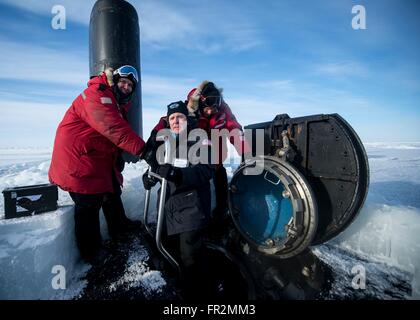 U.S Secretary of the Navy Ray Mabus, center, greets the captain and chief of boat as he emerges from the hatch of - Stock Photo
