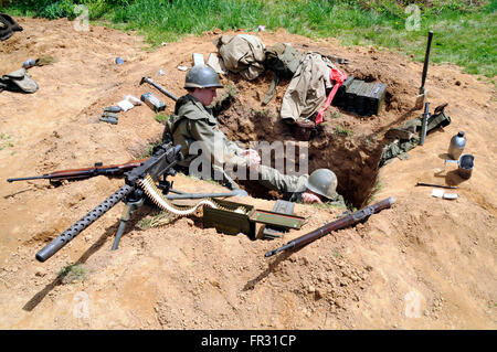 US soldiers in a sniper's nest during a reenactment of World War II - Stock Photo