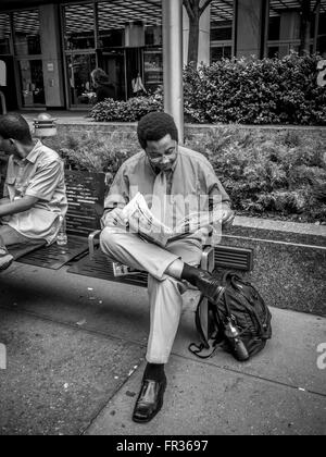 Businessman sat on bench outdoors reading newspaper, New York City, USA. - Stock Photo
