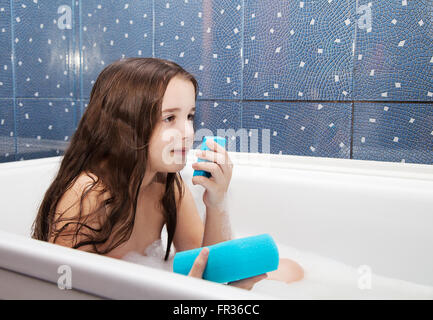 little smiling girl with long brown hair holding blue soap and sponge sitting in the bath - Stock Photo