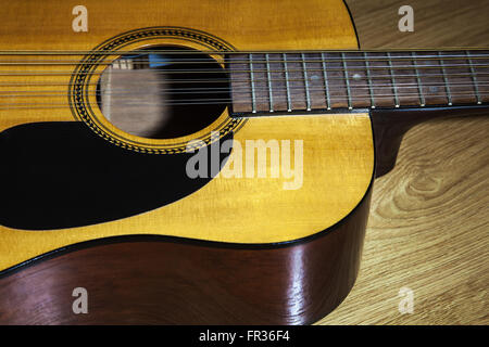 body part of yellow 12 string guitar lying on the wooden floor closeup Stock Photo