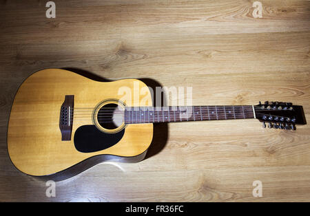 yellow acoustic 12-strings guitar lying on wooden floor closeup Stock Photo