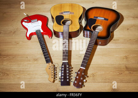 two acoustic and one electric guitars lying on wooden floor Stock Photo