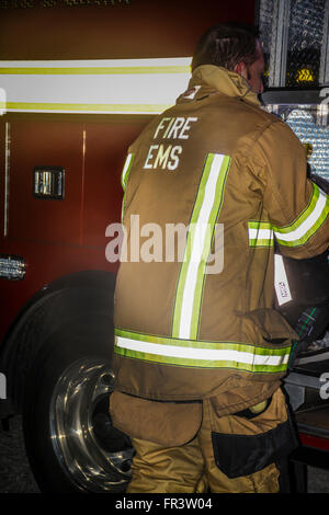 A fireman in uniform works during an emergency situation with his EMS truck during a night time situation - Stock Photo