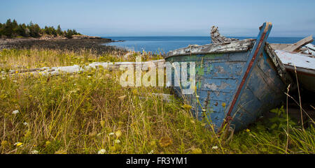 old wrecked boat on grassy coastline in prince edward island canada - Stock Photo