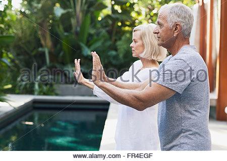 senior couple doing Tai Chi by pool - Stock Photo
