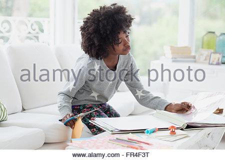 preteen girl working on scrapbook - Stock Photo