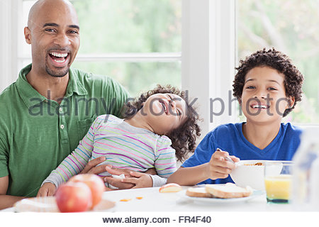 handsome father and young sons at breakfast table - Stock Photo