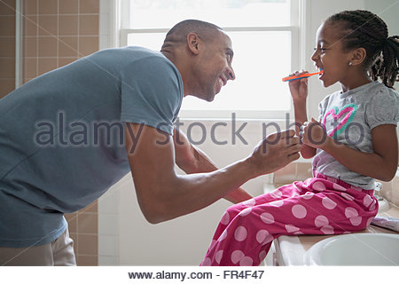 father watching young daughter brushing her teeth - Stock Photo