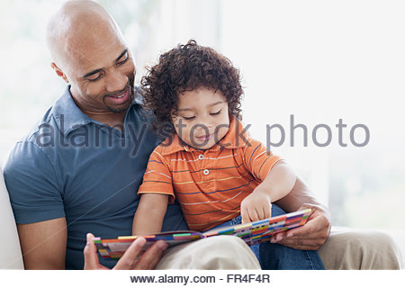 toddler sitting in fathers lap with book - Stock Photo